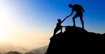 personne aidant une autre à franchir les derniers mètres d'une ascension